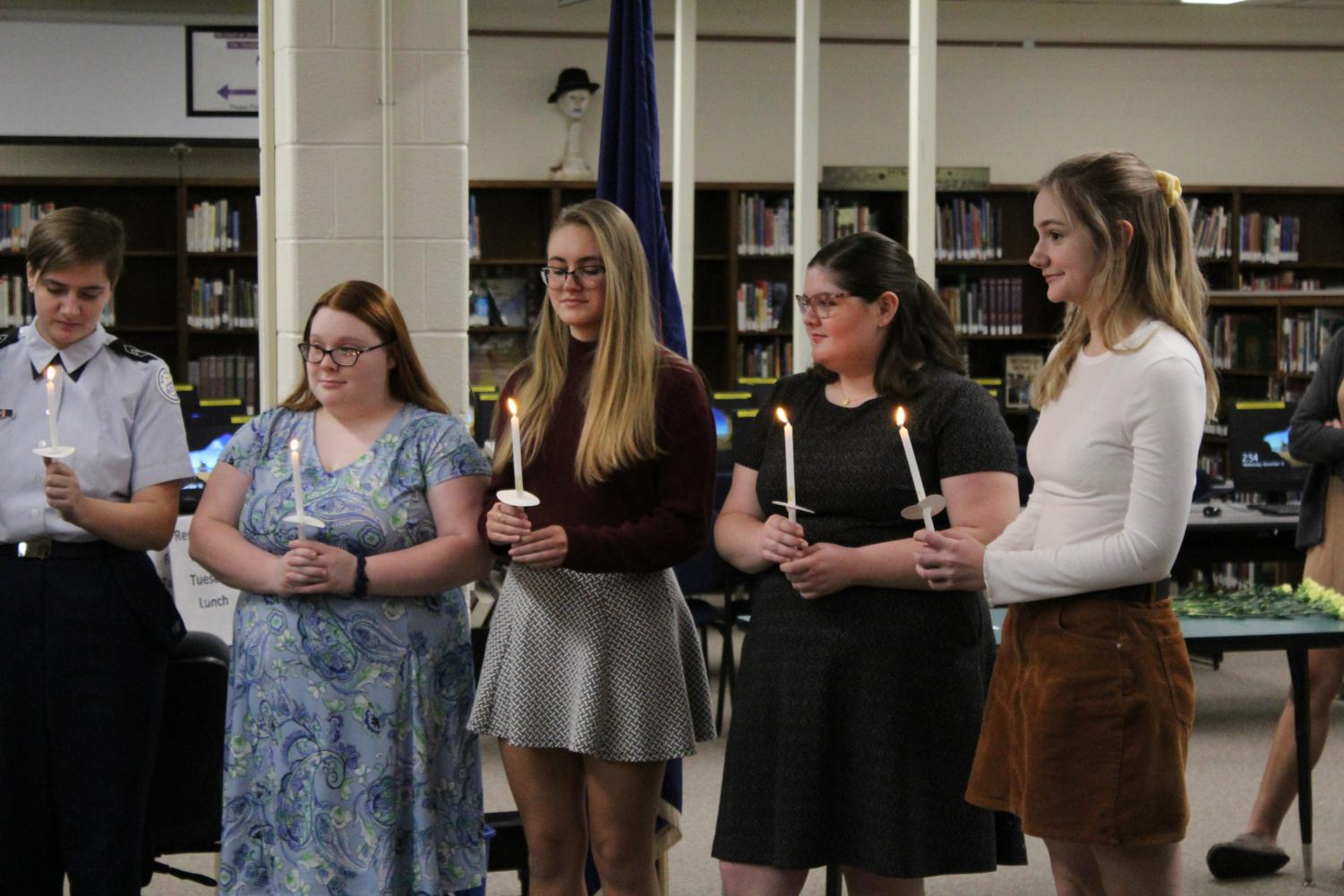 New inductees hold candles at the ceremony.