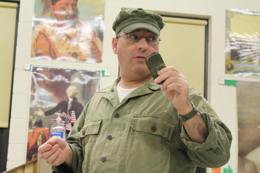 Chris Garcia shows the class a medical kit that American soldiers carried during the war.